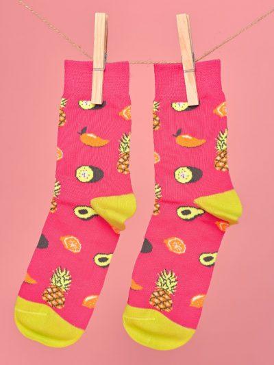Pink-sárga zokni avokádó és ananász mintával lógatva