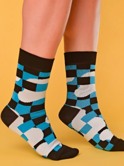 Kék-fekete-fehér zokni geometriai mintával lábon