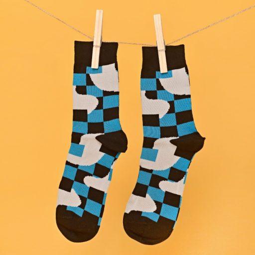 Kék-fekete-fehér zokni geometriai mintával lógatva