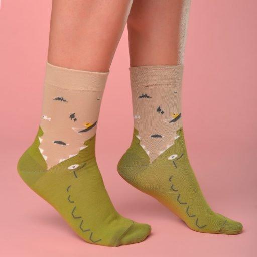 Bézs-zöld zokni ami egy krokodilt formáz lábon