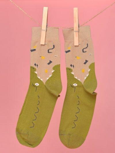 Bézs-zöld zokni ami egy krokodilt formáz lógatva