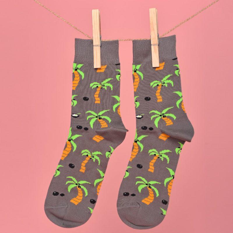 Szürke zokni pálmás és kókuszos mintával lógatva