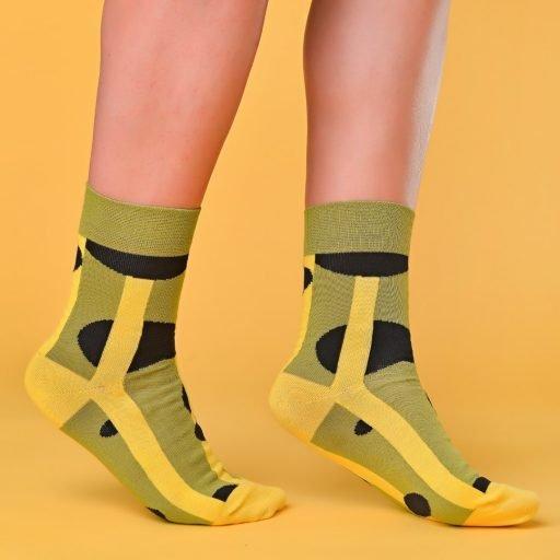 Zöld-sárga-fekete zokni geometriai mintával lábon
