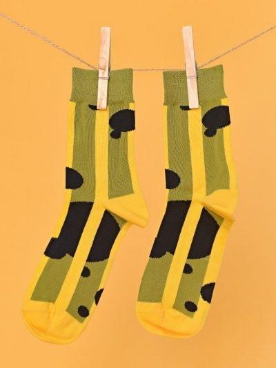 Zöld-sárga-fekete zokni geometriai mintával lógatva